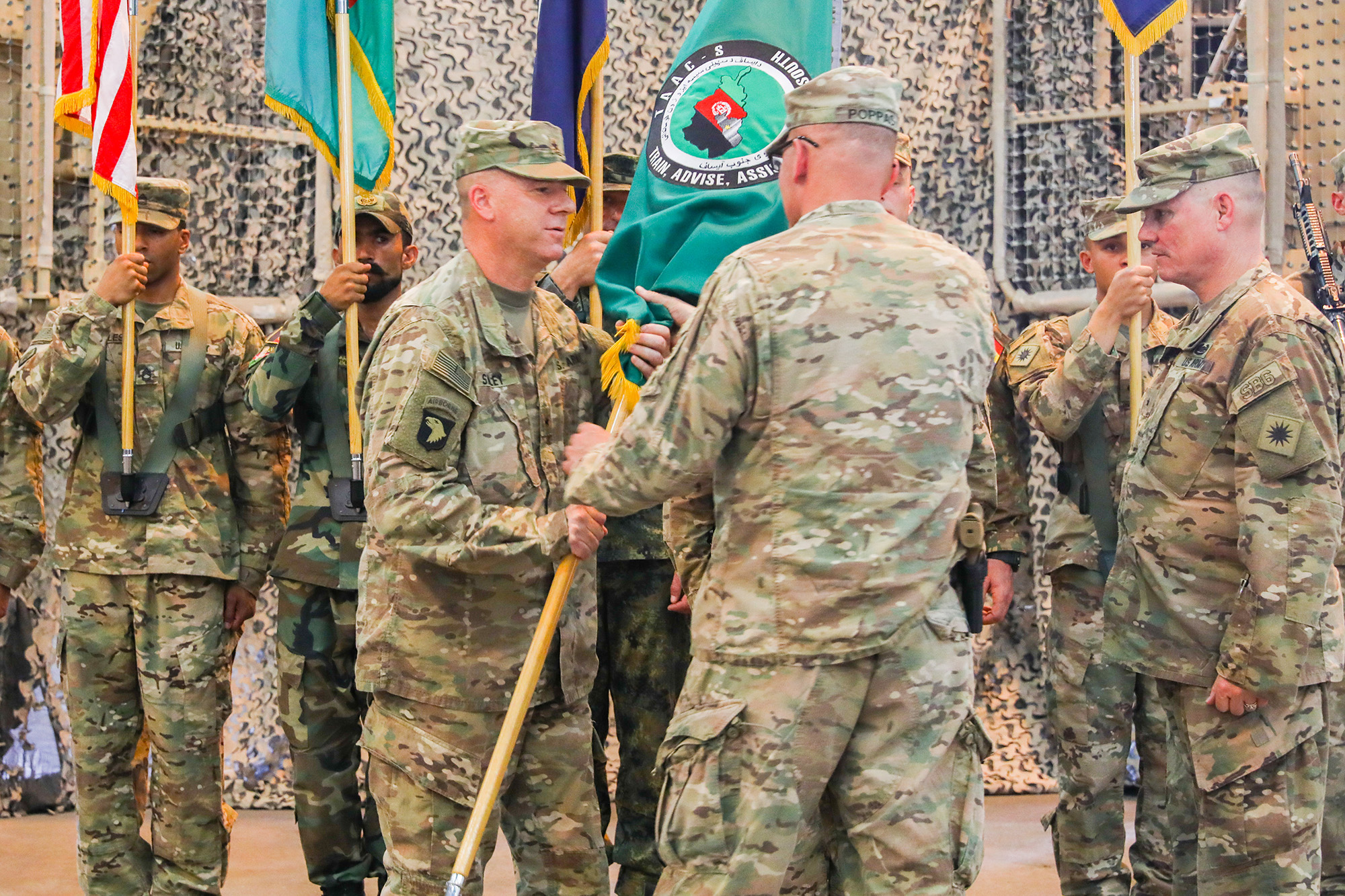 Army Maj. Gen. Andrew Poppas hands the Train, Advise and Assist Command-South colors to Army Brig. Gen. Jeffrey Smiley, incoming commander for TAAC-South on June 30, 2018 during a transfer of authority ceremony in Kandahar, Afghanistan. (Staff Sgt. Neysa Canfield/Army)