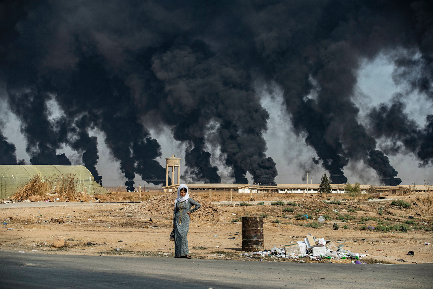 A woman stands along the side of a road on the outskirts of the town of Tal Tamr near the Syrian Kurdish town of Ras al-Ain along the border with Turkey on Oct. 16, 2019, with the smoke plumes of tire fires billowing in the background to decrease visibility for Turkish warplanes that are part of Operation Peace Spring. (Delil Souleiman/AFP via Getty Images)