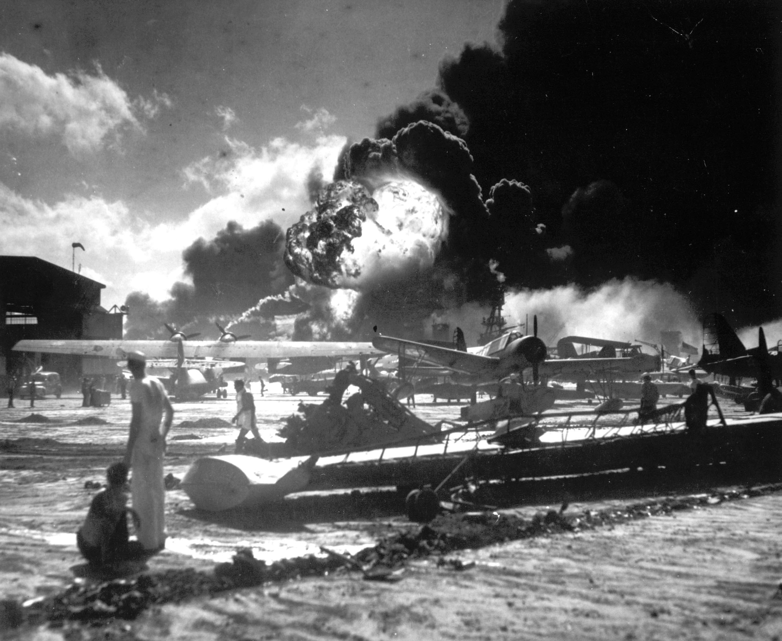In this image provided by the U.S. Navy, sailors stand among wrecked airplanes at Ford Island Naval Air Station as they watch the explosion of the USS Shaw in the background, during the Japanese surprise attack on Pearl Harbor, Hawaii, on December 7, 1941. (AP Photo/U.S. Navy)