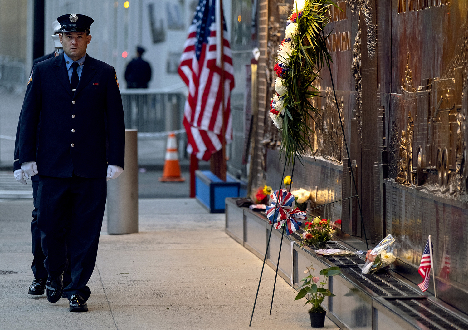 New York City firefighters take a position in front of a memorial on the side of a firehouse adjacent to One World Trade Center and the 9/11 Memorial site during ceremonies commemorating the 18th anniversary of the 9/11 terrorist attacks in New York on Wednesday, Sept. 11, 2019. (Craig Ruttle/AP)