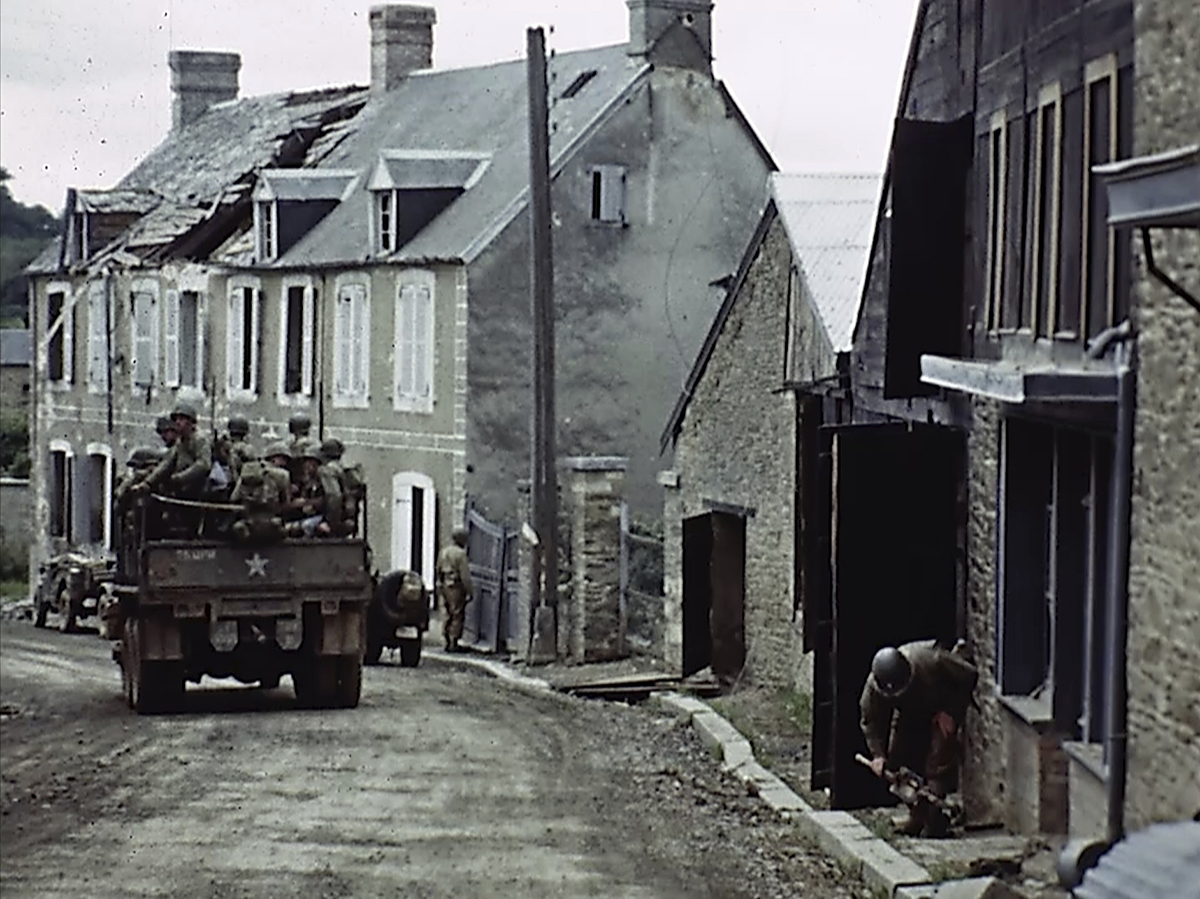 U.S. troops drive through a town during World War II in France. Seventy-five years later, surprising color images of the D-Day invasion and aftermath bring an immediacy to wartime memories. They were filmed by Hollywood director George Stevens and rediscovered years after his death. (War Footage From the George Stevens Collection at the Library of Congress via AP)