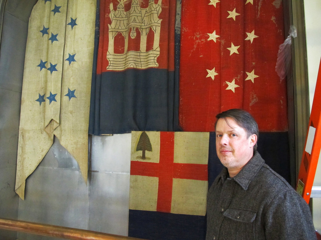 In this Thursday, Dec. 7, 2017 photo, Charles Swift, managing director and curator of the U.S. Naval Academy Museum, stands in front of a case in Annapolis, Md., where the flags shown behind him had been tucked away from view behind another flag on display for nearly 100 years. The flags were recently moved out of the cases for preservation. (Brian Witte/AP)