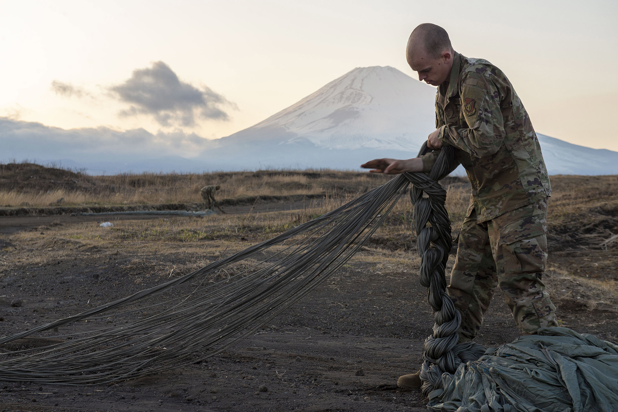 Staff Sgt. Nicholas Adkins folds parachute suspension lines on March 25, 2020, before stowing the parachute inside a recovery bag at the Combined Arms Training Center, Camp Fuji, Japan. (Senior Airman Gabrielle Spalding/Air Force)
