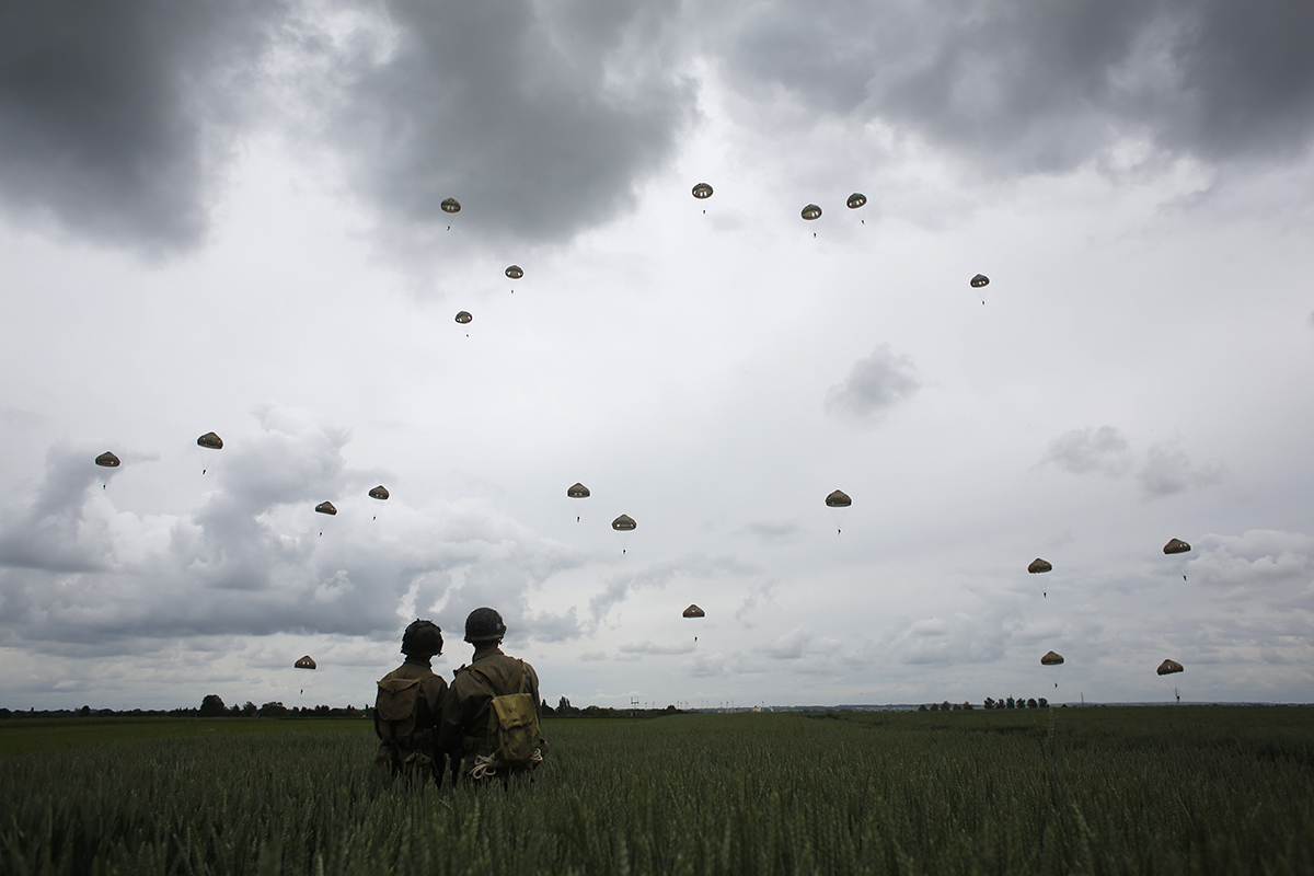 WWII enthusiasts watch French and British parachutists jumping during a commemorative parachute jump over Sannerville, Normandy, Wednesday, June 5, 2019. Extensive commemorations are being held in the U.K. and France to honor the nearly 160,000 troops from Britain, the United States, Canada and other nations who landed in Normandy on June 6, 1944, in history's biggest amphibious invasion. (Thibault Camus/AP)