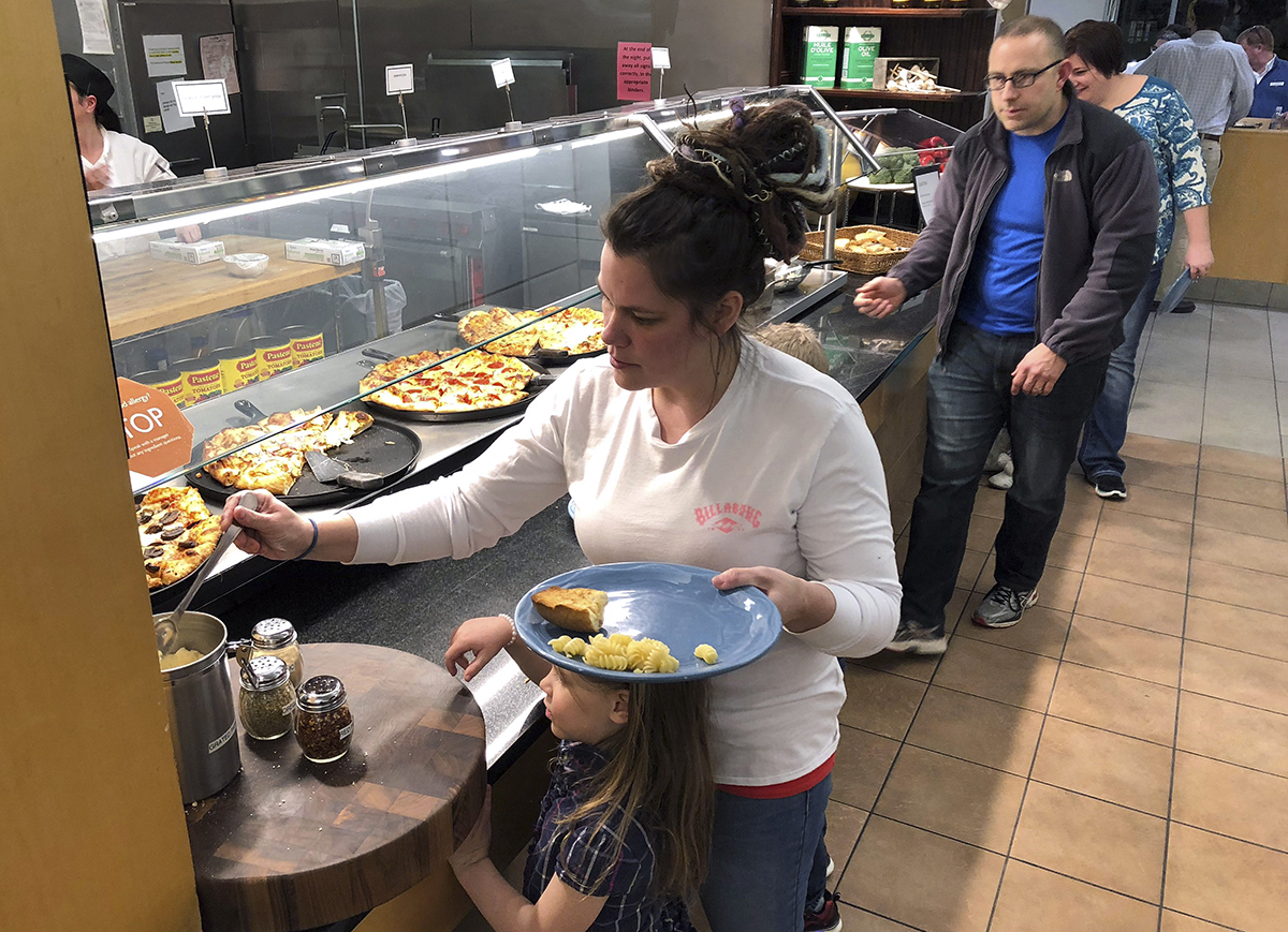 U.S. Coast Guard spouse Rachel Malcom, left, gathers food for herself and her daughter, Tuesday, Jan. 15, 2019, at Roger Williams University in Bristol, R.I. The college offered a free dinner for active-duty Coast Guard members and their families in Rhode Island and southeastern Massachusetts who are working without pay during the partial federal shutdown. (Jennifer McDermott/AP)