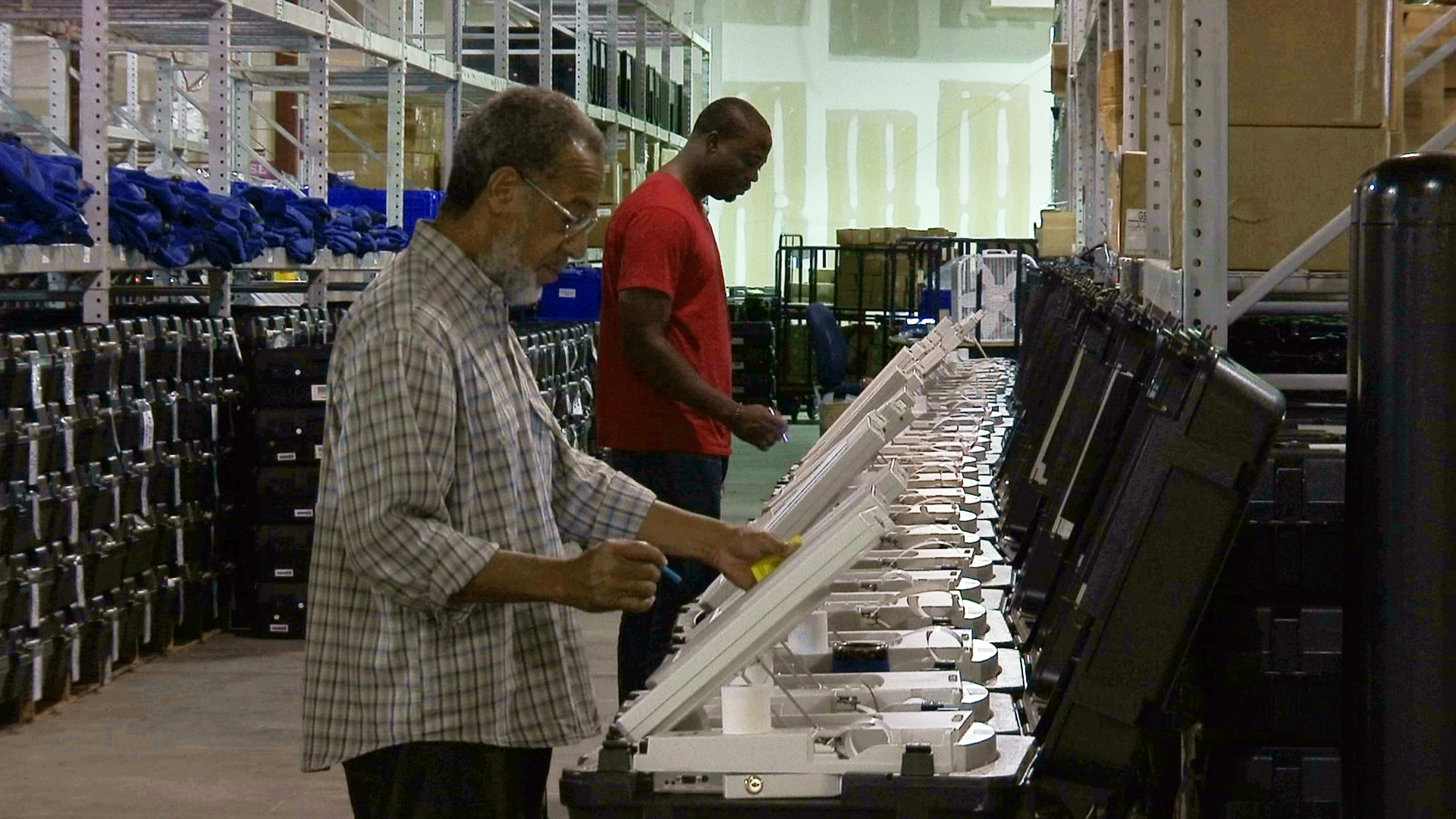 This Sept. 22, 2016 file photo shows employees of the Fulton County Election Preparation Center in Atlanta test electronic voting machines. A bill in the House would establish directives for states to harden election cybersecurity, auditing and means to pair votes cast electronically with a visible paper record. (Alex Sanz/AP)