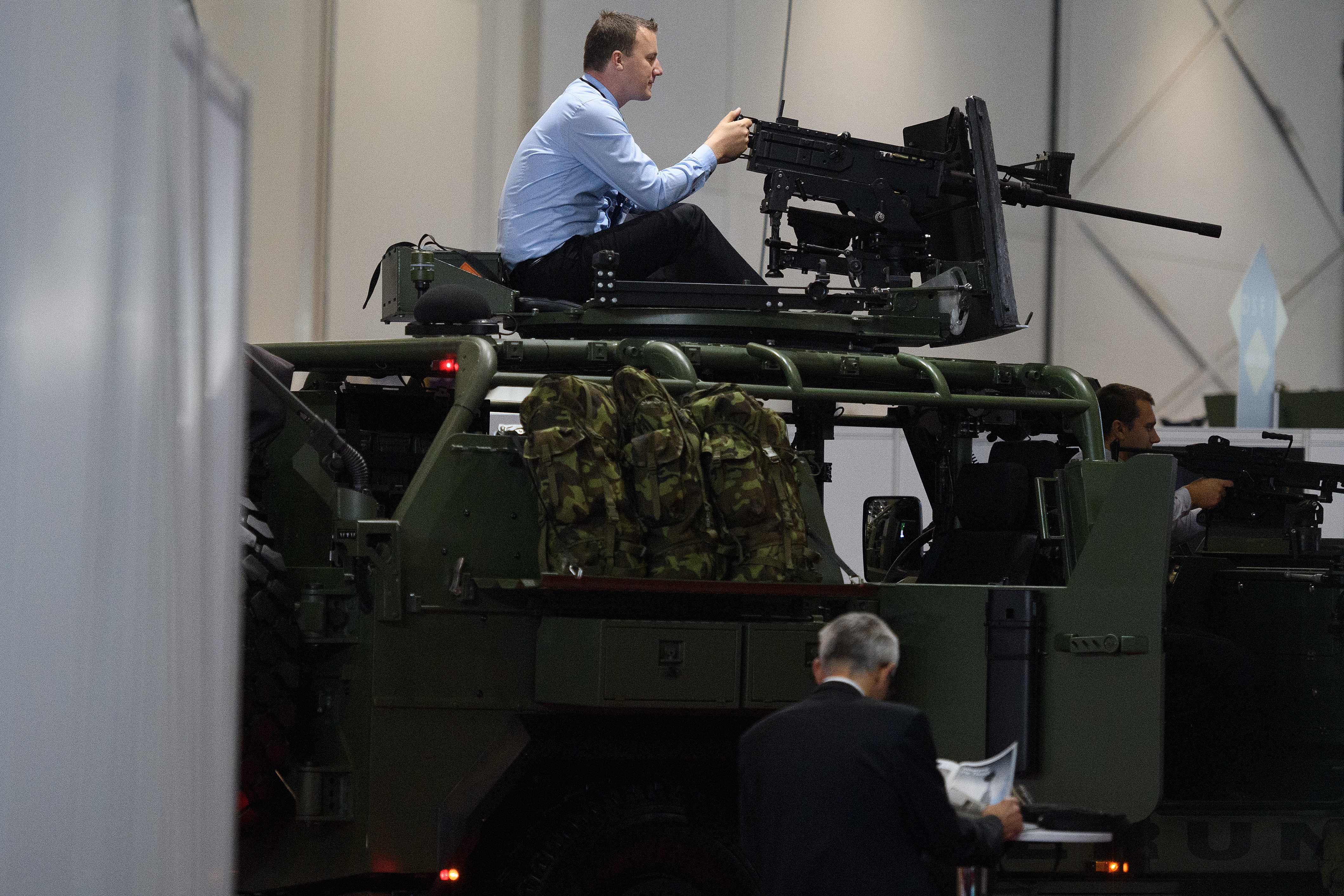 A man tests the gun mounted on an SVOS Perun armored vehicle on Sept. 11, 2019, at DSEI. (Leon Neal/Getty Images)