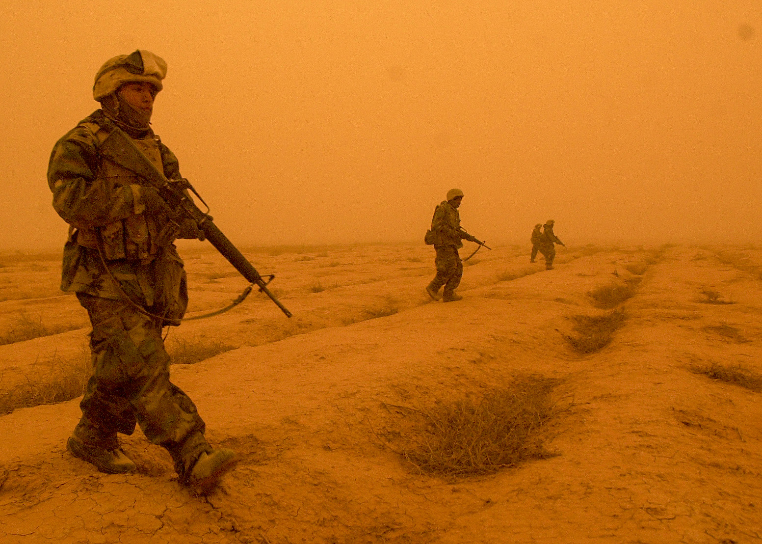 Lance Cpl. Alfredo Martinez, 21, from Lindsay, CA with battery M, 3rd Battalion, 11th Marine Regiment with fellow Marines patrol outside the artillery position in central Iraq to make sure it is safe for the artillery convey to head to another area on March 26, 2003. (Jud McCrehin/Marine Corps Times)