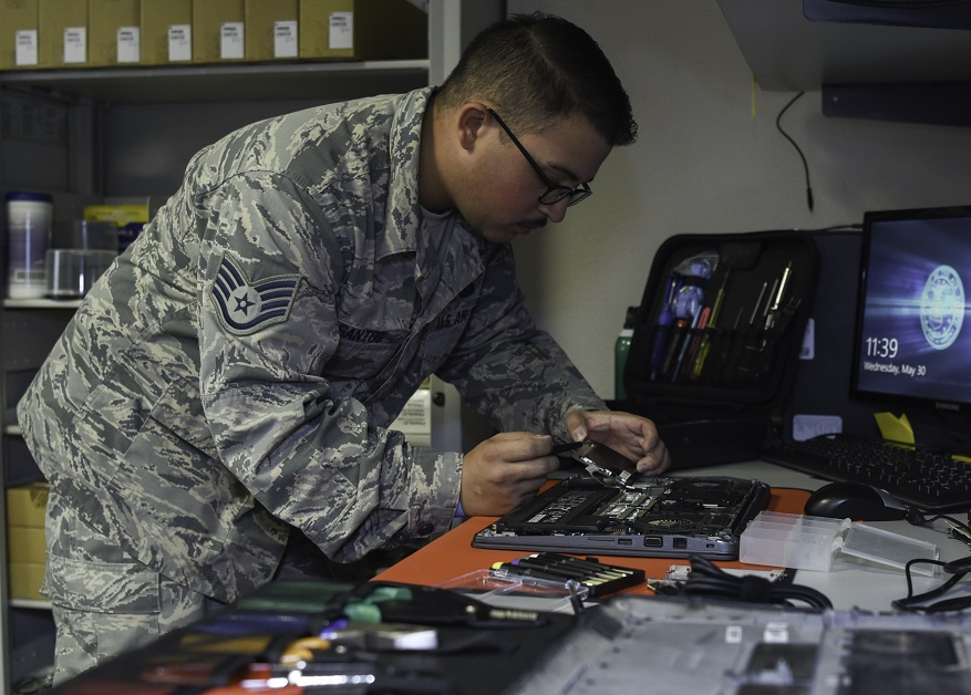 U.S. Air Force Staff Sgt. Leo Santos, a client systems technician with the 823rd RED HORSE Squadron, removes a hard drive from a laptop. (/Airman 1st Class Ronald Feliciano Rivera/U.S. Air Force)