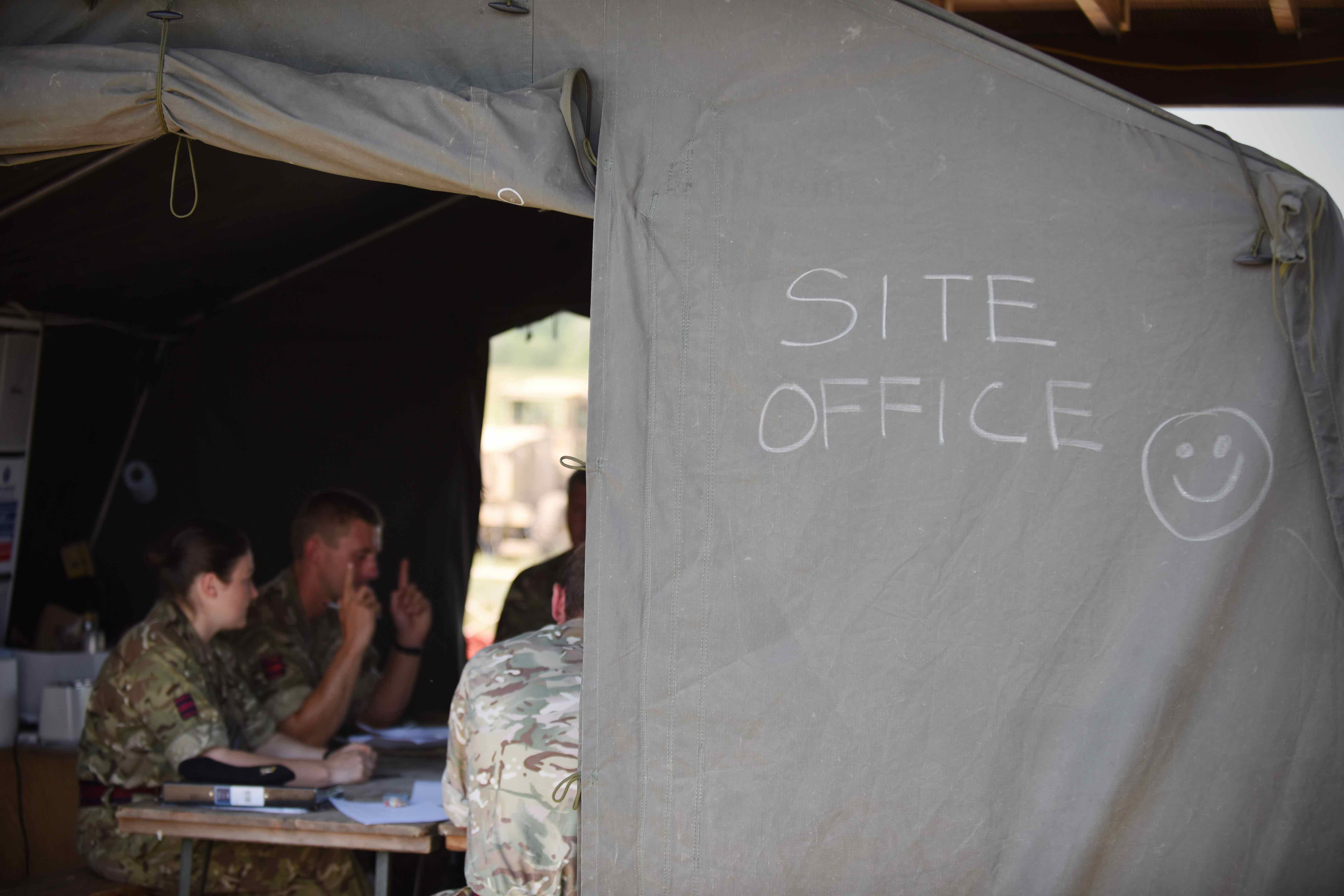 Engineers discuss construction plans inside a tent. While the soldiers encountered interoperability issues from language barriers to using the metric system, they quickly adapted to varying procedures and learned to communicate, even through a form of sign language. (Jen Judson/Staff)