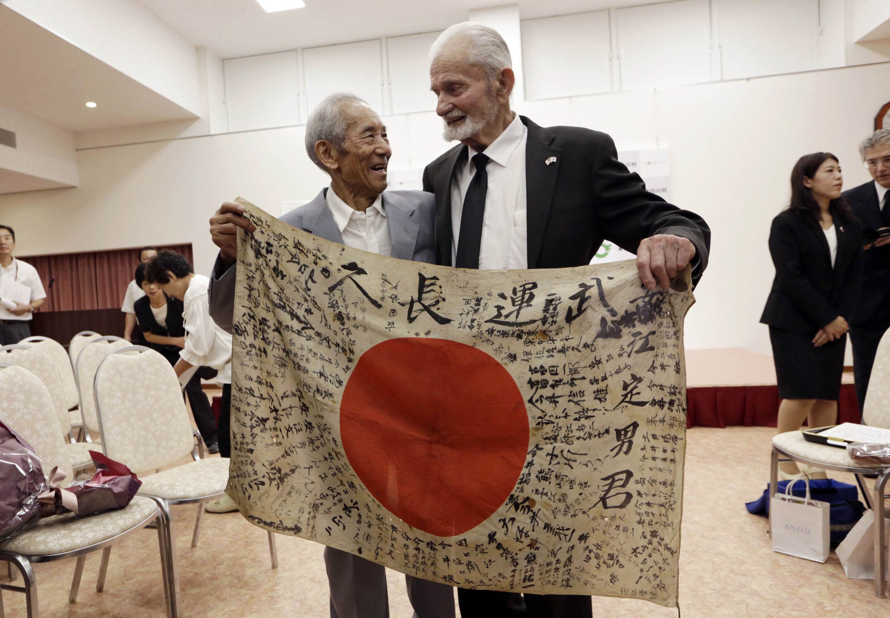 WWII veteran Marvin Strombo, right, and Tatsuya Yasue, 89-year-old farmer, hold a Japanese flag with autographed messages which was owned by his brother Sadao Yasue, who was killed in the Pacific during World Work II, during a ceremony in Higashishirakawa, in central Japan's Gifu prefecture Tuesday, Aug. 15, 2017. Strombo has returned to the fallen soldier's family the calligraphy-covered flag he took from the man's body 73 years ago. (Eugene Hoshiko/AP)