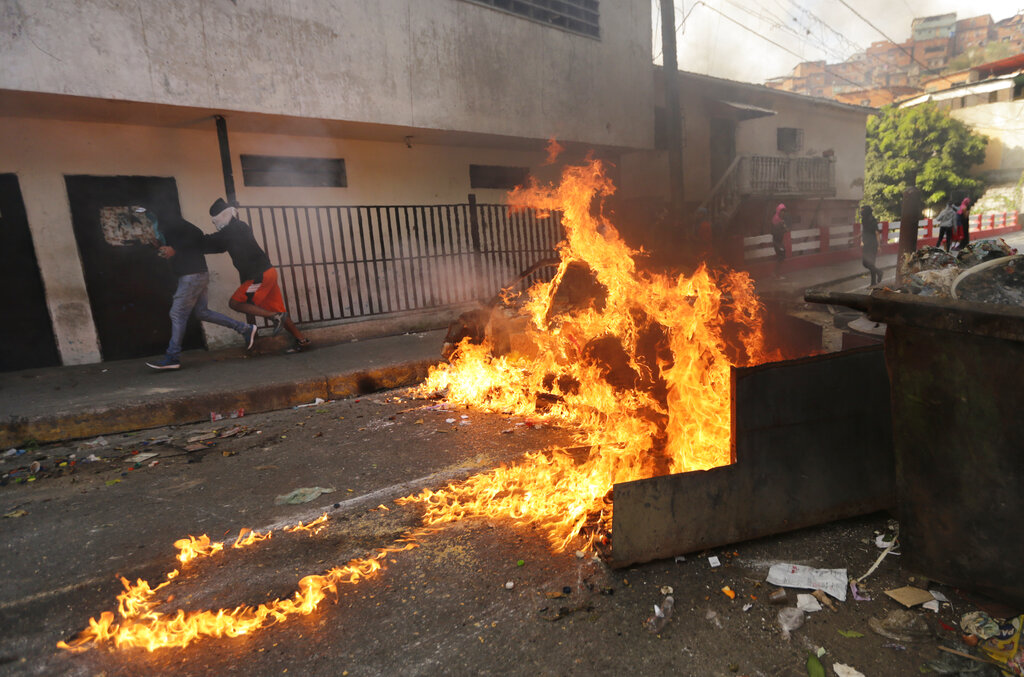A roadblock set up by anti-government protesters burns during clashes with security forces after an apparent mutiny by a national guard unit in the Cotiza neighborhood of Caracas, Venezuela, on Monday. (Fernando Llano/AP)