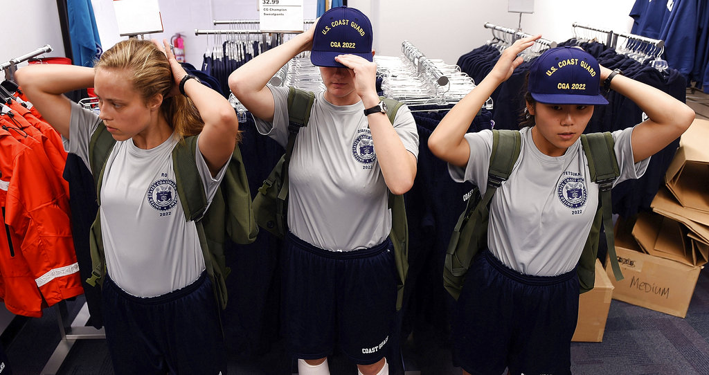 X-Ray Two company swabs Katherine Roys, left, Sophia Stafford, center, and Kalea Tetsuka try on their new ball caps during uniform issues as the U.S. Coast Guard Academy Class of 2022 reports for Day 1 of Swab Summer on July 2, 2018 at the academy in New London, Conn. (Sean D. Elliot/The Day via AP)