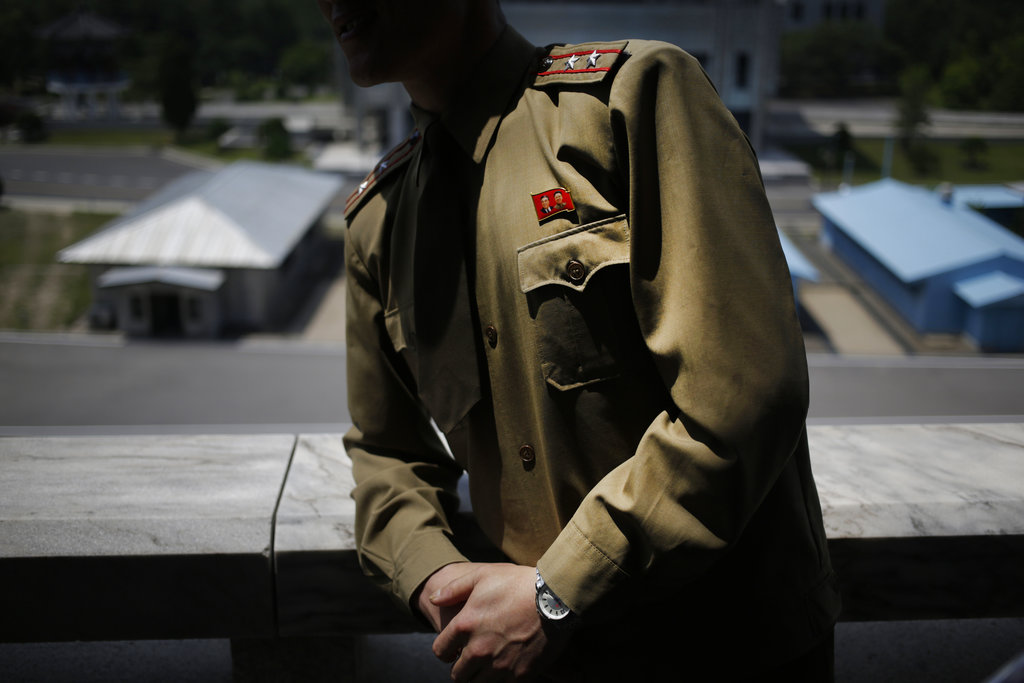 North Korean Army Lt. Colonel Hwang Myong Jin wears a pin of late North Korean leaders Kim Il Sung and his son Kim Jong Il while explaining the history of the truce village at the Demilitarized Zone (DMZ) which separates the two Koreas in Pammunjom, North Korea, Wednesday, June 20, 2018. Hwang who has been a guide on the northern side of the Demilitarized Zone that divides the two Koreas for five years says that since the summits between North Korean leader Kim Jong Un and the presidents of South Korea and the United States, things have quieted down noticeably in perhaps the most iconic symbol of the one last place on Earth where the Cold War still burns hot. (Dita Alangkara/AP)