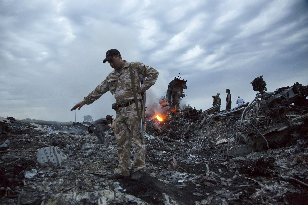People walk among the debris at the crash site of Malaysian Airlines Flight MH17 near the village of Grabovo, Ukraine, on July 17, 2014. (Dmitry Lovetsky/AP)