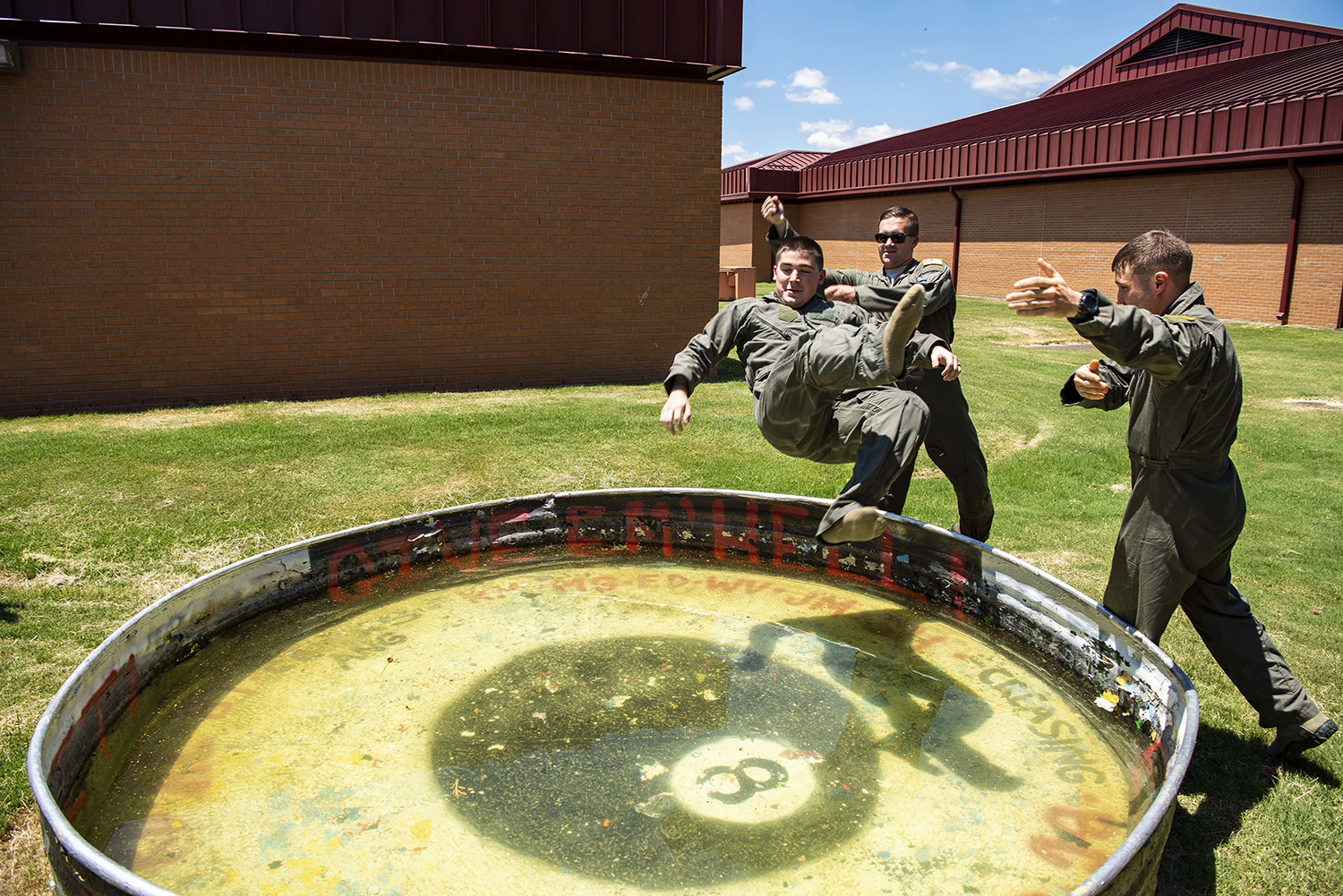2nd Lt. Corey Persons is thrown into a solo tank by fellow student pilots 2nd Lt. Graham McAninich and 2nd Lt. Kyle Blanchette on July 15, 2019, at Vance Air Force Base, Okla. It is Air Force tradition to be thrown into the solo tank upon completion of a student pilot's first solo flight. (Senior Airman Taylor Crul/Air Force)