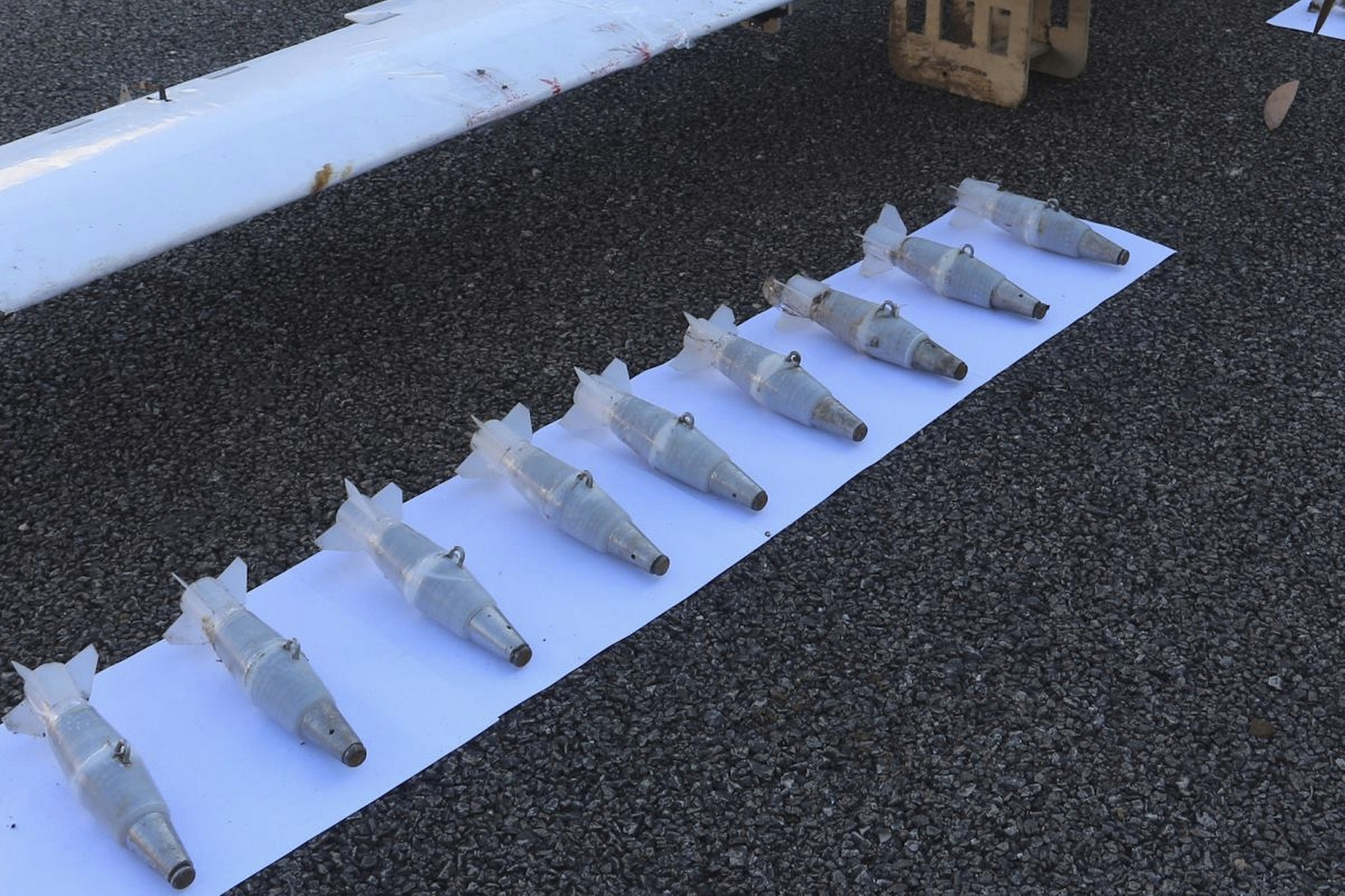 Mortar shells are lined up next to one of the drones that was forced to land after an unsuccessful attack attempt at Hemeimeem air base in Syria. (Russian Defence Ministry Press Service via AP)