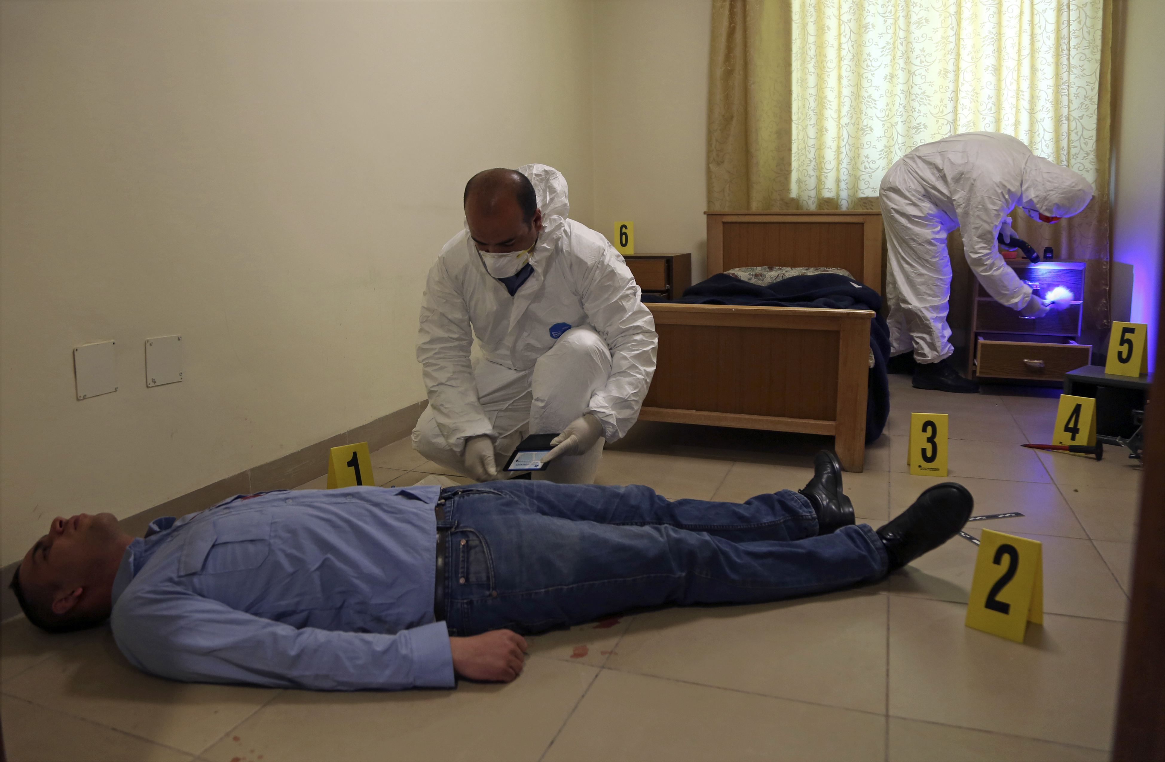 Jordanian crime scene technicians dust for fingerprints as part of a drill held at the nation's Forensic Science Laboratory, in Amman, Jordan, on March 19, 2018. The lab is part of an upgrade of Jordan's fight against suspected militants and criminals. (Raad Adayleh/AP)