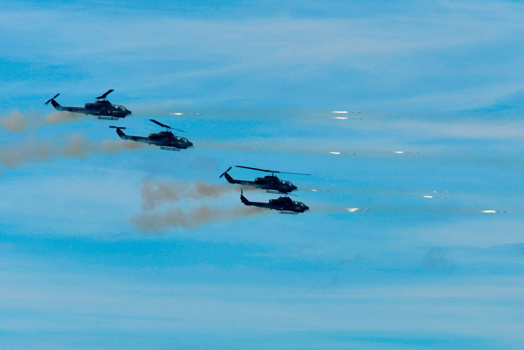 Four US-made Bell AH-1W Supercobra helicopters launch rockets during the 35th