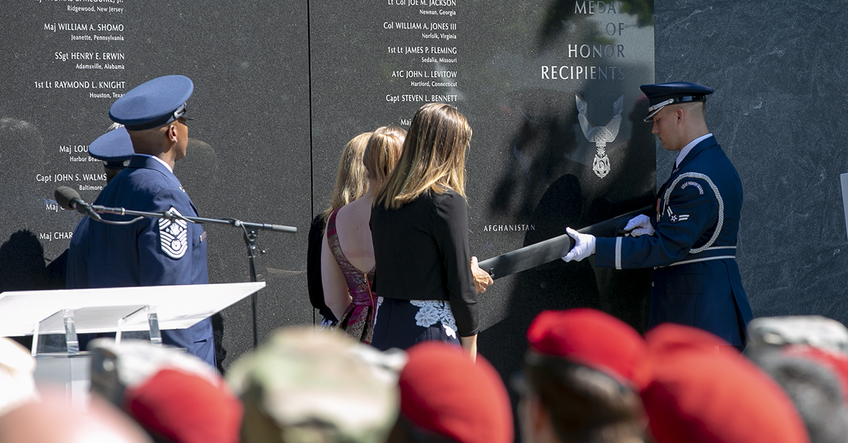 Valerie Nessel, spouse of U.S. Air Force Tech. Sgt. John Chapman, along with daughters Brianna and Madison, removes cover from her husband's engraved name during a Medal of Honor unveiling ceremony at the Air Force Memorial. Chapman, was posthumously awarded the MOH on Wednesday for actions on Takur Ghar mountain in Afghanistan on March 4, 2002. (Alan Lessig/Staff)