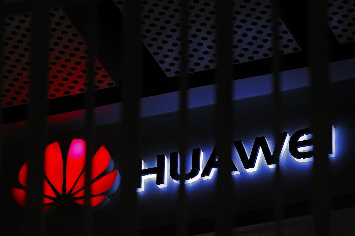 A logo of Huawei retail shop is seen through a handrail inside a commercial office building in Beijing. (AP Photo/Andy Wong, File)