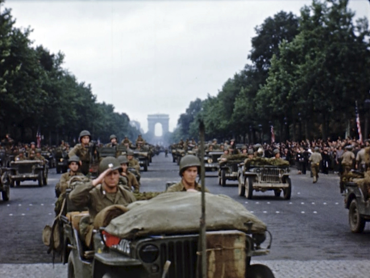U.S. military vehicles and soldiers march down the Champs-Elysees after the liberation of Paris. Seventy-five years later, surprising color images of the D-Day invasion and aftermath bring an immediacy to wartime memories. They were filmed by Hollywood director George Stevens and rediscovered years after his death. (War Footage From the George Stevens Collection at the Library of Congress via AP)