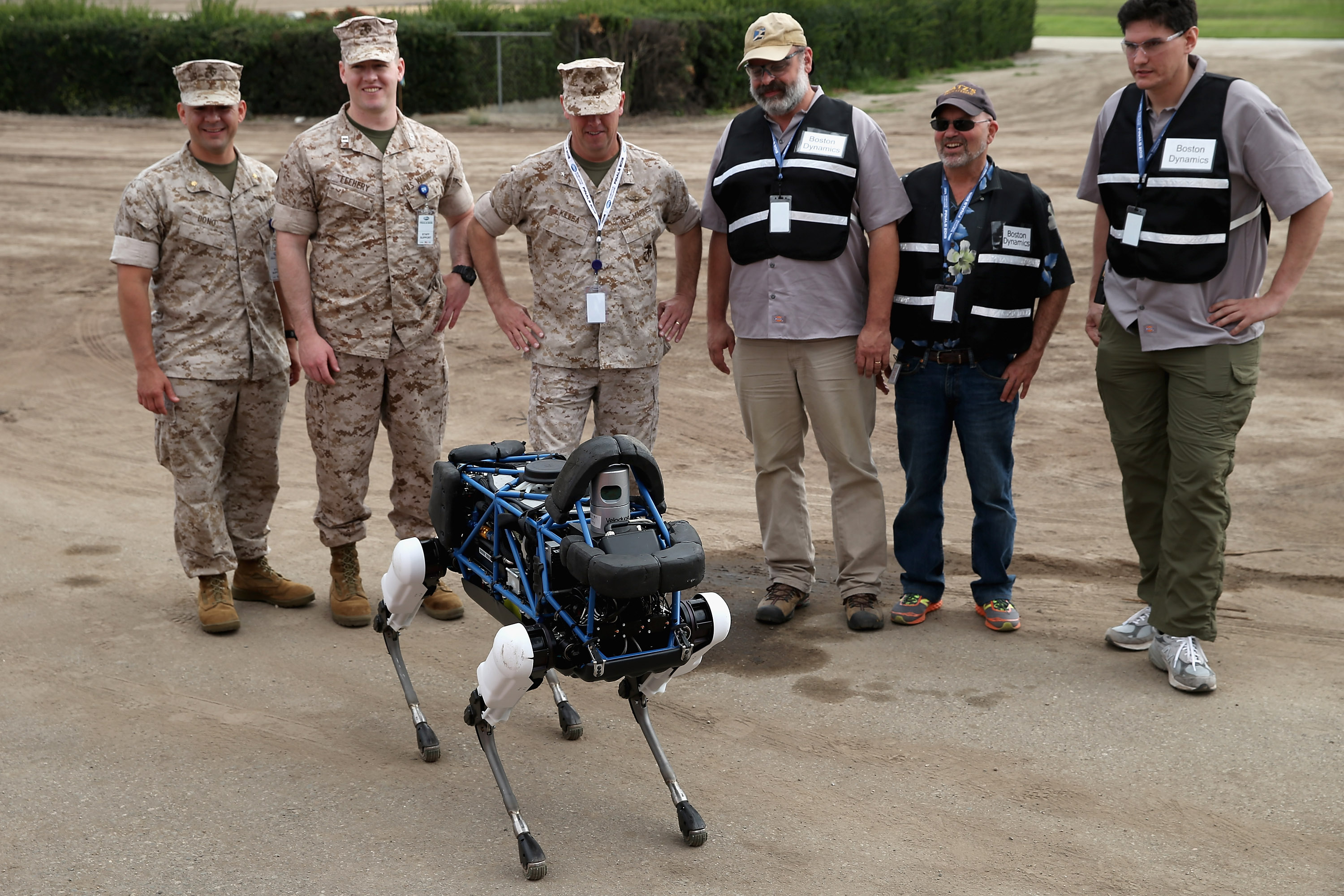 United States Marines and representatives from Boston Dynamics look at Spot, a four-legged robot designed for indoor and outdoor operation, during the Defense Advanced Research Projects Agency Robotics Challenge at the Fairplex June 5, 2015 in Pomona, California.(Photo by Chip Somodevilla/Getty Images)