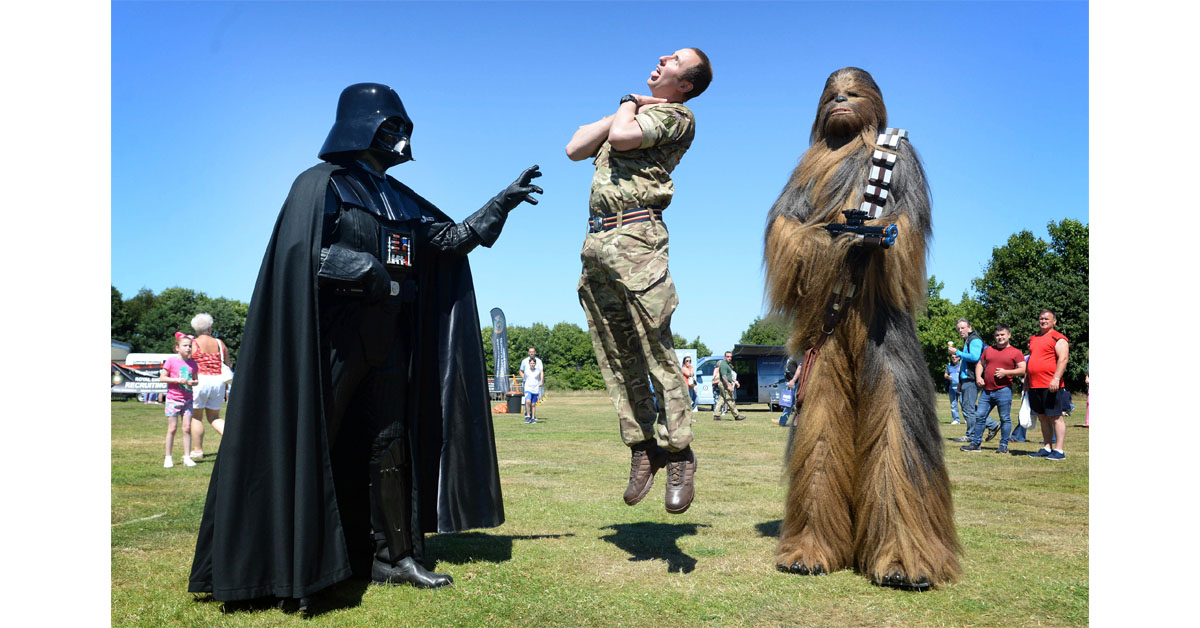 Military Recovery mechanic Ian Pew, center, clashes with a man dressed as Star Wars character Darth Vader as they put on a show as part of the National Armed Forces Day in Stirling, England, on June 30, 2018. (Mark Owens/British Ministry of Defence via AP)