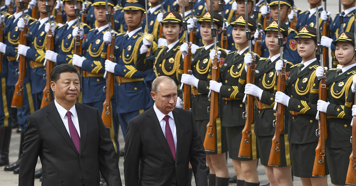 Russian President Vladimir Putin, center, reviews a military honor guard with Chinese President Xi Jinping, left, during a welcoming ceremony outside the Great Hall of the People in Beijing on June 8, 2018. (Greg Baker/AFP via Getty Images)