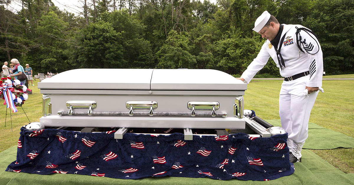 Navy MA1 Robert Linke, stationed at Naval Weapons Station Earle in Colts Neck, New Jersey, pauses at the casket of Seaman 1st Class Edward Slapikas, killed while serving aboard the USS Oklahoma in the attack on Pearl Harbor in December 1941. Slapikas' remains were identified earlier this year and returned to Luzerne County for burial 77 years after his death. (Christopher Dolan/The Citizens' Voice via AP)