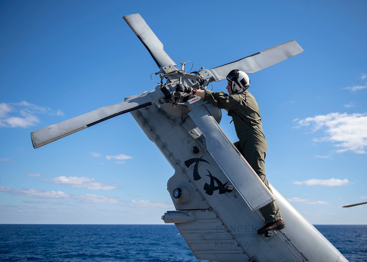 Lt. Austin Gallegos verifies tail rotor integrity on a MH-60R Sea Hawk on July 19, 2019, aboard the Ticonderoga-class guided-missile cruiser USS Chancellorsville (CG 62) in the Coral Sea. (Mass Communication Specialist 2nd Class John Harris/Navy)