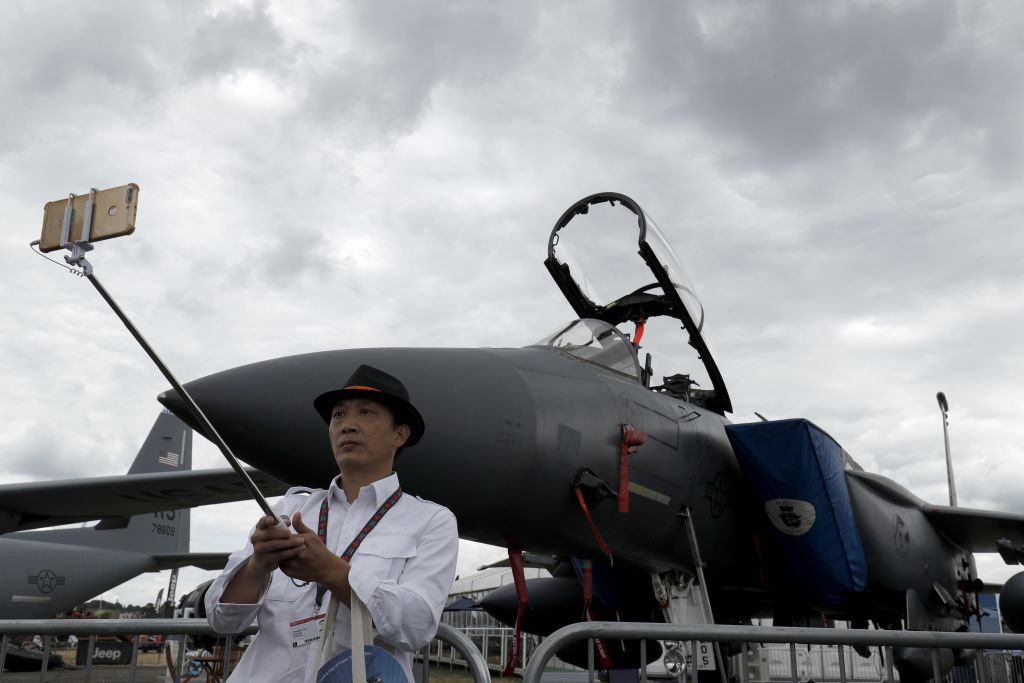 A visitor of the Farnborough Airshow takes a selfie in front of a Boeing F-15E fighter. (Adrian Dennis/AFP via Getty Images)
