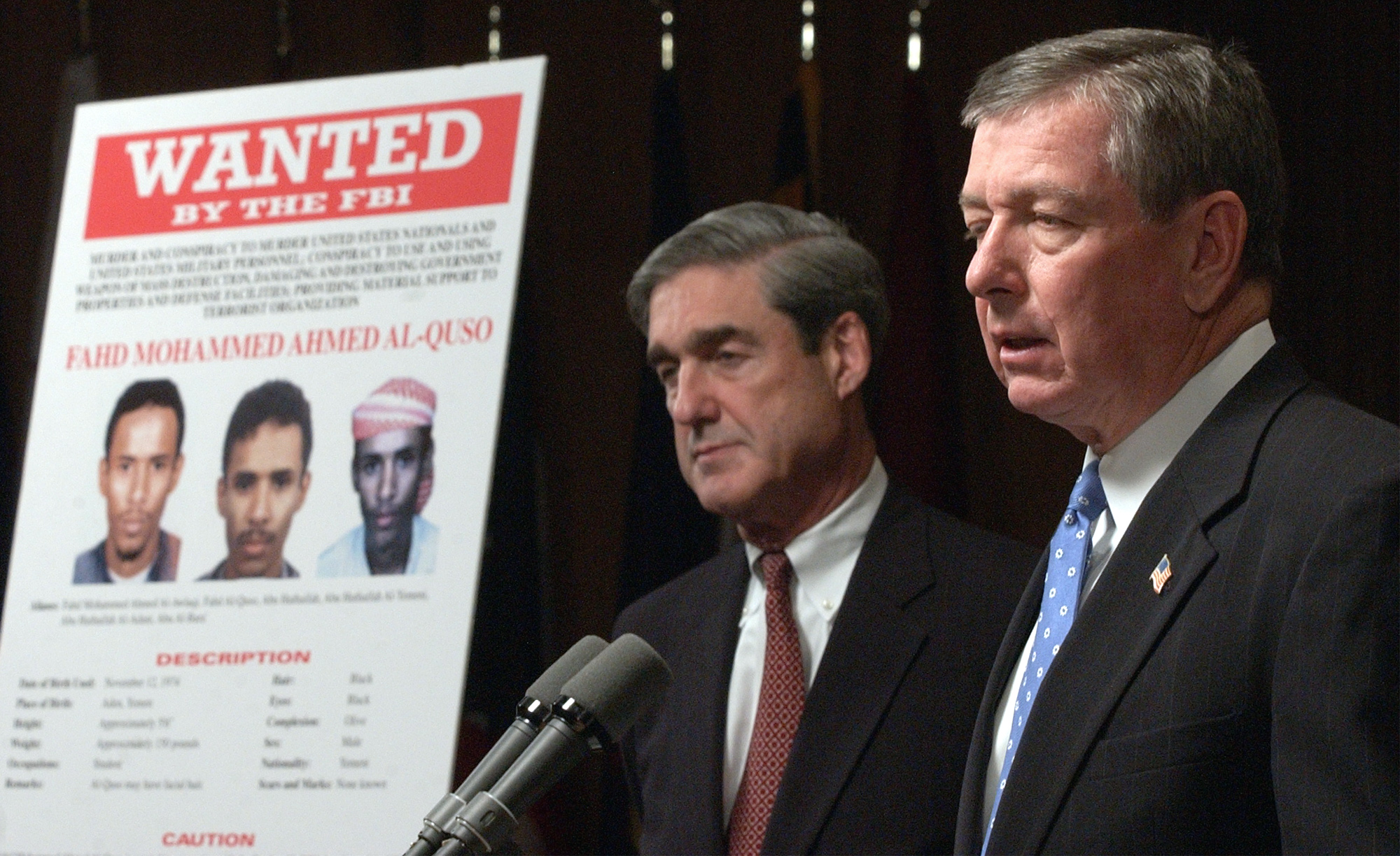 Attorney General John Ashcroft, right, accompanied by FBI Director Robert Mueller, announces at FBI headquarters in Washington Thursday, May 15, 2003 that Fahd Al-Quso, shown in wanted poster at left, and Jamal Ahmed Mohammed al-Badawi were charged Thursday as al-Qaida members who helped plan the attack on the USS Cole that killed 17 American sailors in 2000. Both Al-Quso and al-Badawi were charged with 50 counts of various terrorism offenses, including the murders of U.S. nationals and U.S. military personnel. If convicted, they could face the death penalty. (AP Photo/Susan Walsh)
