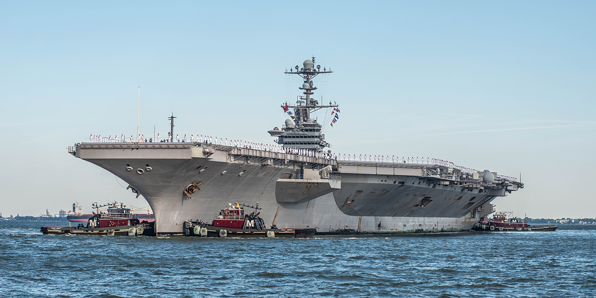 Tugboats work the bow of the aircraft carrier John C. Stennis as the ship arrives pierside in Norfolk. (Mark D. Faram/Staff)