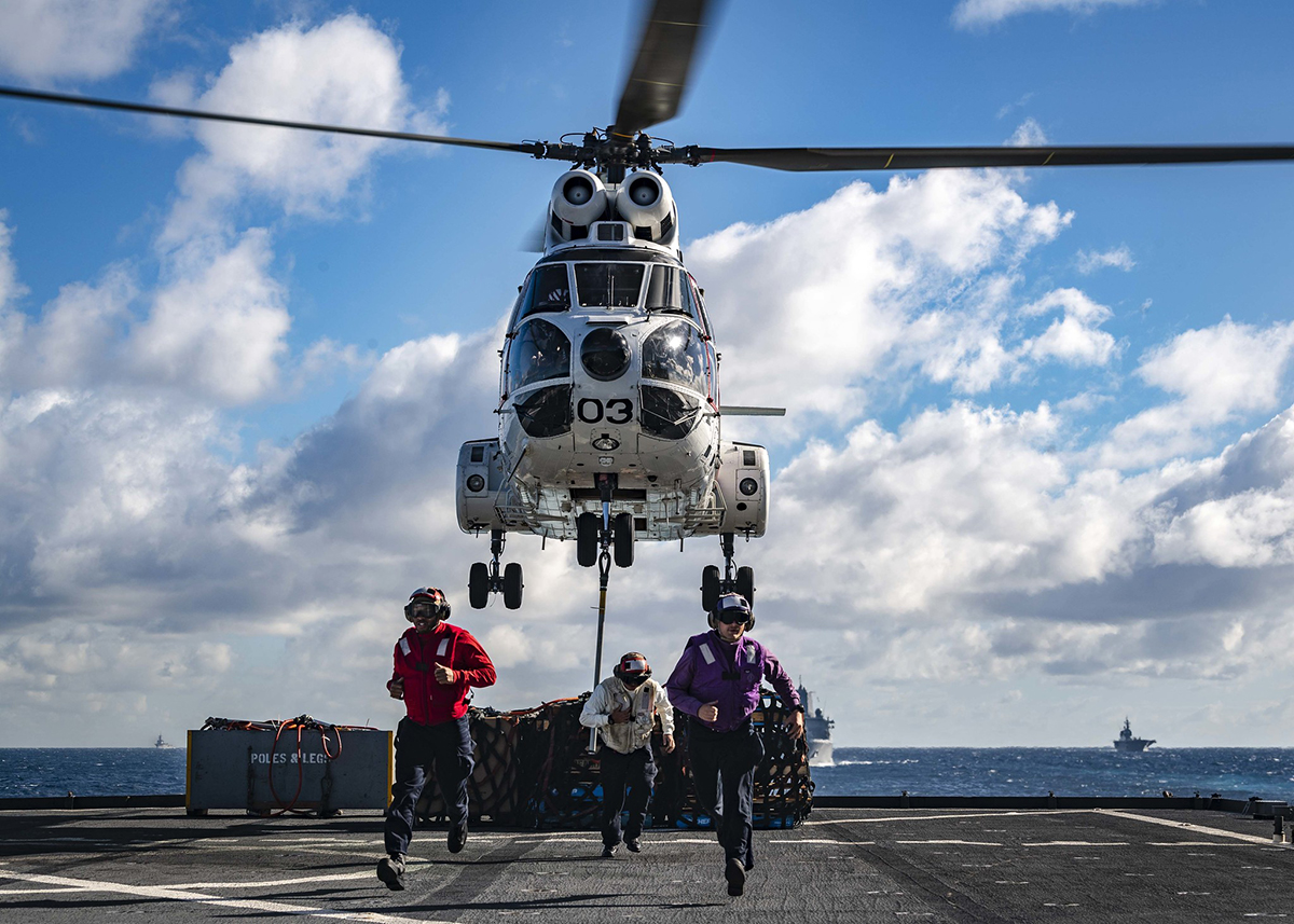 Sailors run past the foul line as a SA-330J Puma picks up pallets from the flight deck of the amphibious dock landing ship USS Ashland (LSD 48) on June 25, 2019, prior to a replenishment-at-sea with the amphibious assault ship USS Wasp (LHD 1) and fleet replenishment oiler USNS Rappahannock (T-AO 204). (Mass Communication Specialist 2nd Class Markus Castaneda/Navy)
