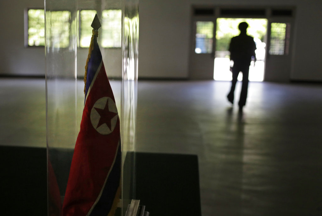 A North Korean soldier is silhouetted in the background while the national flag is displayed at the museum of the armistice agreement between North and South Korea at the truce village of Panmunjom at the Demilitarized Zone (DMZ) which separates the two Koreas in Panmunjom, North Korea, Wednesday, June 20, 2018. (Dita Alangkara/AP)