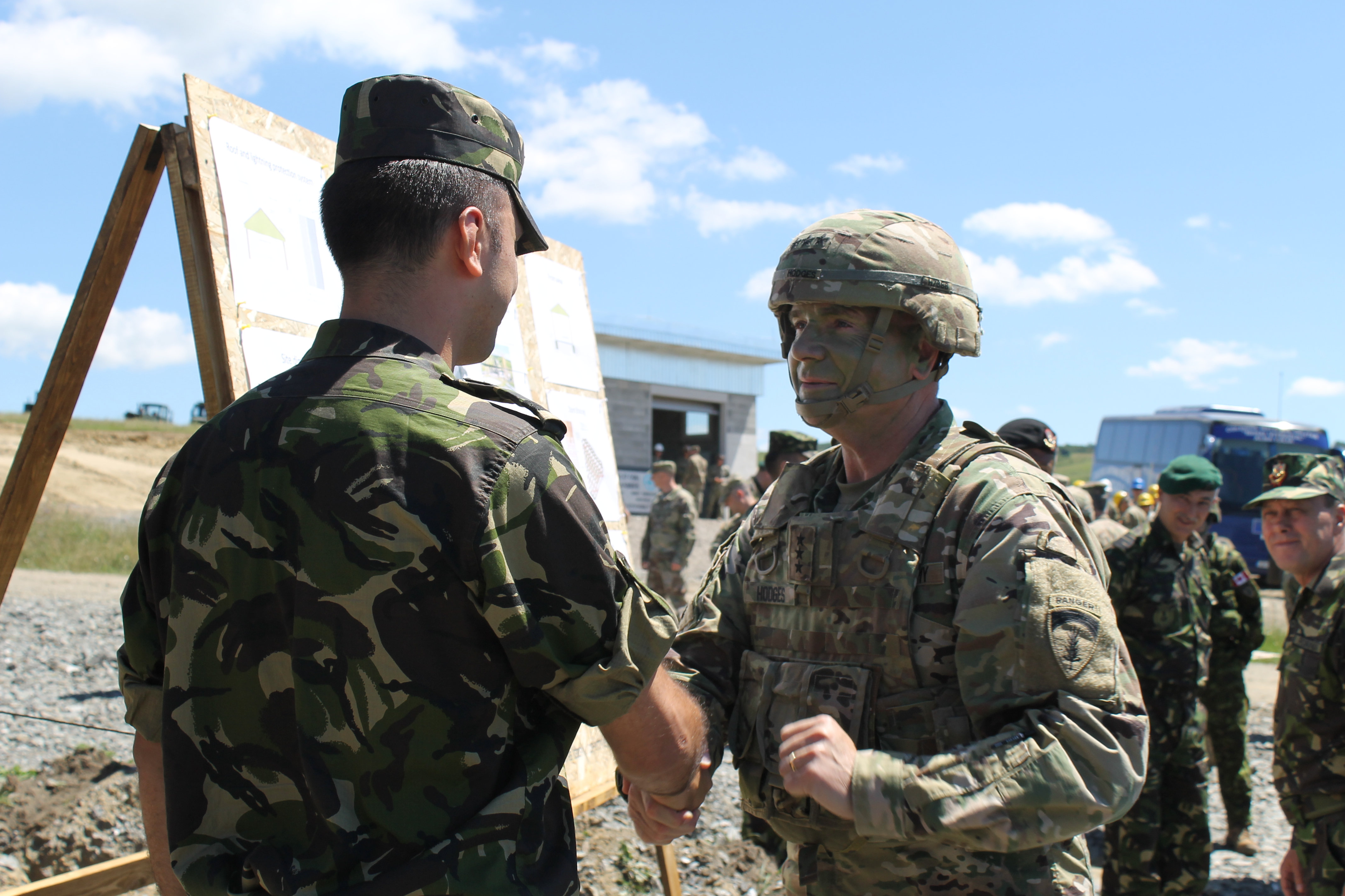 Lt. Gen. Ben Hodges gives a Romanian soldier a coin following the soldier's presentation on the multipurpose structure as part of Resolute Castle. The soldiers were challenged to build the facilities by an onslaught of rain storms throughout the spring and summer but were nearing completion on most projects by July 14 in time for a distinguished visitors day. (Jen Judson/Staff)