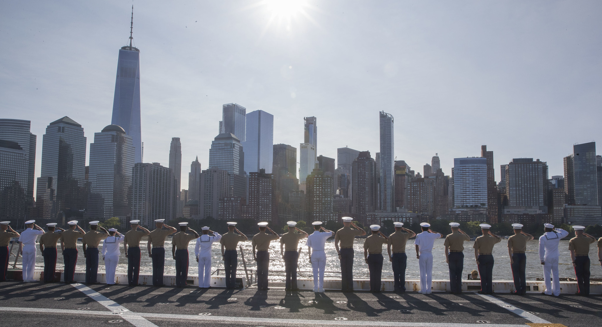 Sailors and Marines salute the Freedom Tower from the flight deck of the amphibious transport dock ship USS New York (LPD 21) on May 22, 2019, while transiting the Hudson River as they head to a pier in Manhattan during Fleet Week New York. (Mass Communication Specialist 2nd Class Ryan Seelbach/Navy)