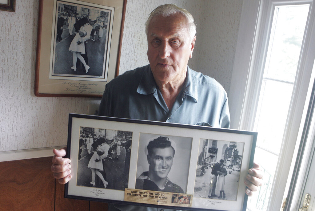 George Mendonsa posed in Middletown, R.I., on July 2, 2009 holding a copy of the famous Alfred Eisenstadt photo of Mendonsa kissing a woman in a nurse's uniform in Times Square on Aug. 14, 1945, while celebrating the end of World War II, left. Mendonsa died Sunday. He was 95. It was years after the photo was taken that Mendonsa and Greta Zimmer Friedman, a dental assistant in a nurse's uniform, were confirmed to be the couple. (Connie Grosch/Providence Journal via AP)