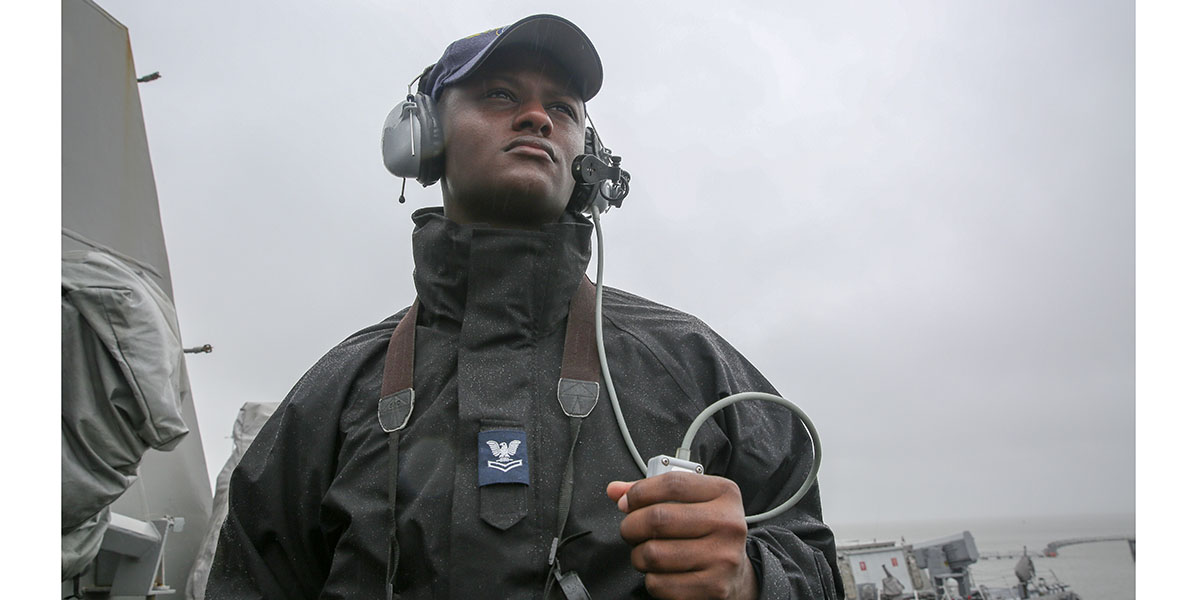 Operations Specialist Seaman Demetrus Jones, assigned to Arleigh Burke-class destroyer USS Truxtun (DDG 103), demonstrates the operational black Gortex parka of a second class petty officer along with the flame-resistant, two-piece organizational clothing.(Mass Communication Specialist 2nd Class Stacy M. Atkins Ricks/Navy)