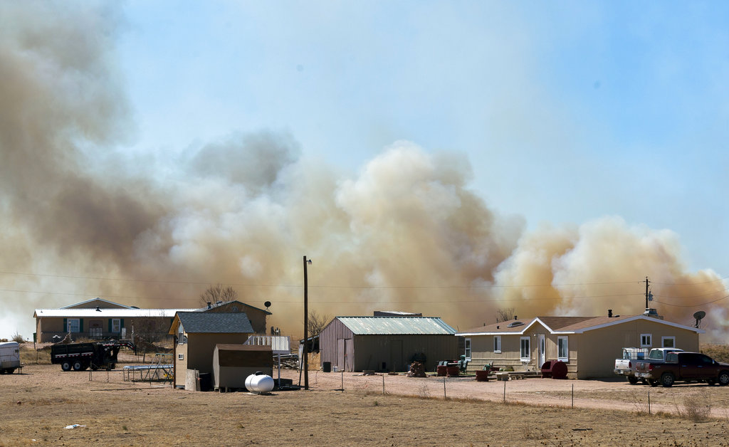 Smoke from a wildfire, named the Carson Midway wildfire, billows behind homes in Hanover, Colo., Friday March 16, 2018. (Dougal Brownlie/The Gazette via AP)