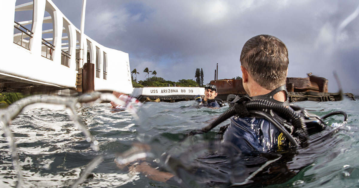 Navy divers assigned to Mobile Diving Salvage Unit (MDSU) 1 dive on the USS Arizona Memorial at Joint Base Pearl Harbor-Hickam. (MC1 Arthurgwain L. Marquez/Navy)