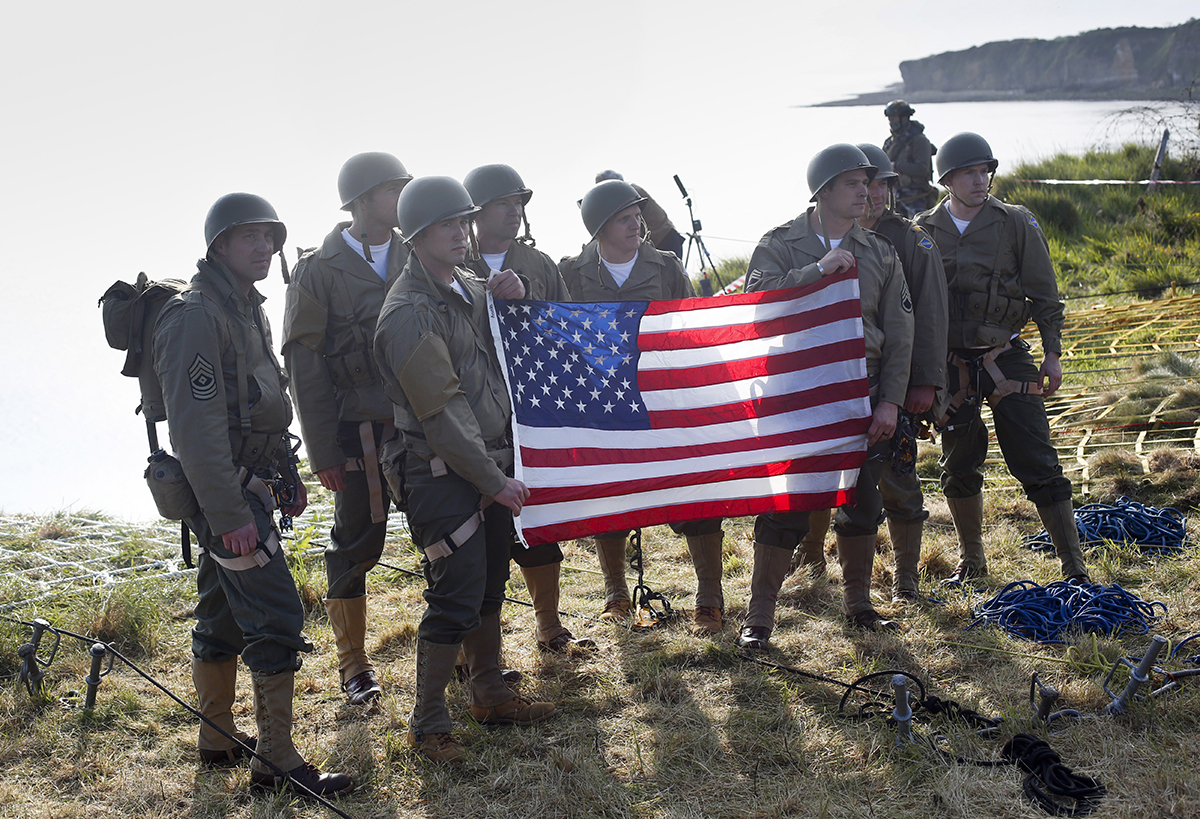 Rangers from the U.S. 75th Ranger Regiment, in period dress, hold the American flag after scaling the cliffs of Pointe-du-Hoc in Cricqueville-en-Bessin, Normandy, France, Wednesday, June 5, 2019. During the American assault of Omaha and Utah beaches on June 6, 1944, U.S. Army Rangers scaled the 100-foot cliffs to seize German artillery pieces that could have fired on the American landing troops. (Thibault Camus/AP)