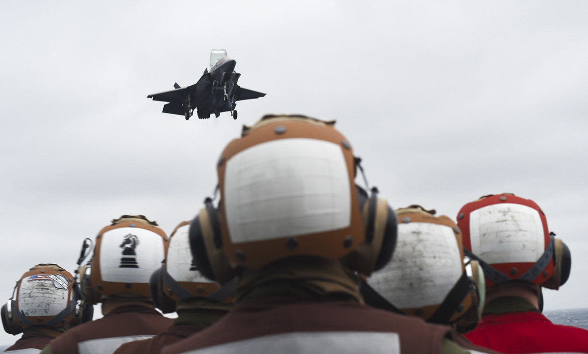 Sailors and Marines observe an F-35B Lightening II with Marine Fighter Attack Squadron (VMFA) 121 fly above the amphibious assault ship USS Wasp (LHD 1), marking the first time the aircraft has deployed aboard a U.S. Navy ship and with a Marine Expeditionary Unit (MEU) in the Indo-Pacific. VMFA-121 is assigned under the Okinawa-based 31st Marine Expeditionary Unit 931st MEU), will remain embarked aboard Wasp for a regional patrol meant to strengthen regional alliances, provide rapid-response capability and advance the Up-Gunned ESG concept. (MC1 Alexandra Seeley/Navy)