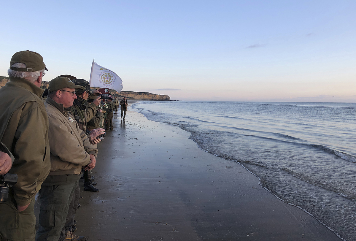 Re-enactors stand at the shore of Omaha Beach at sunrise as part of events to mark the 75th anniversary of D-Day on Omaha Beach in Vierville-sur-Mer, Normandy, France, Thursday, June 6, 2019. World leaders are gathered Thursday in France to mark the 75th anniversary of the D-Day landings. (Cedric Lecoz via AP)