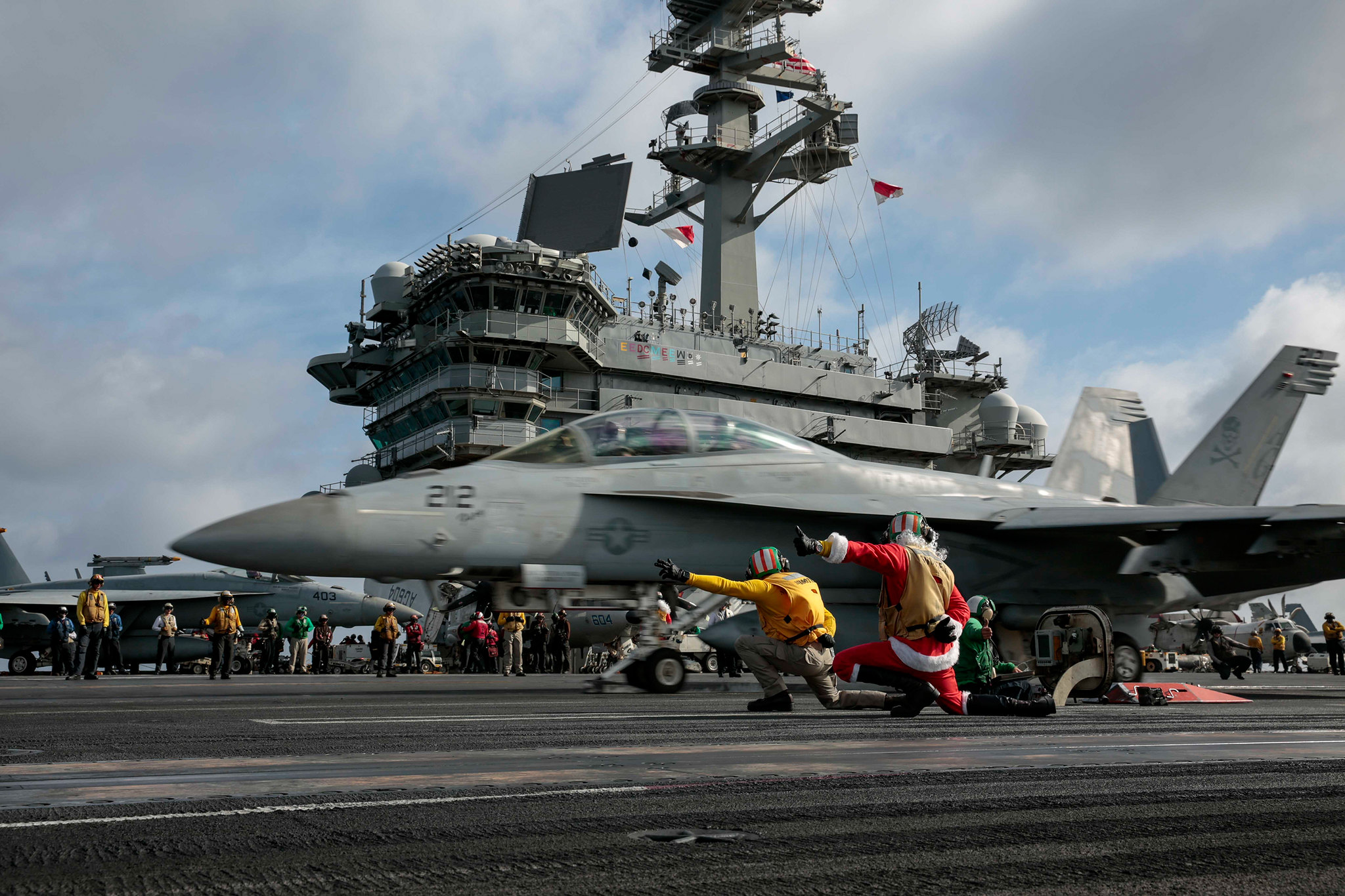 A sailor dressed as Santa Claus directs the launch of an F/A-18F Super Hornet on Dec. 24, 2019, on the flight deck of the aircraft carrier USS Abraham Lincoln (CVN 72) in the South China Sea. (Mass Communication Specialist 3rd Class Michael Singley/Navy)