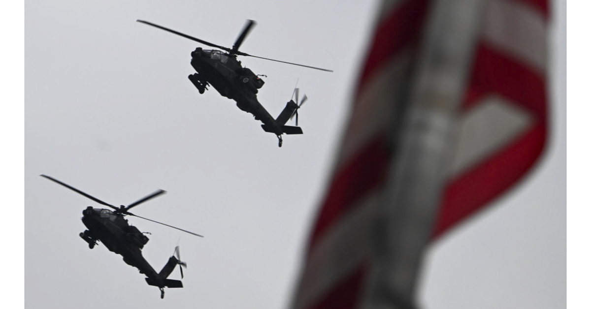 U.S. Army AH-64 Apache attack helicopters fly overhead during the