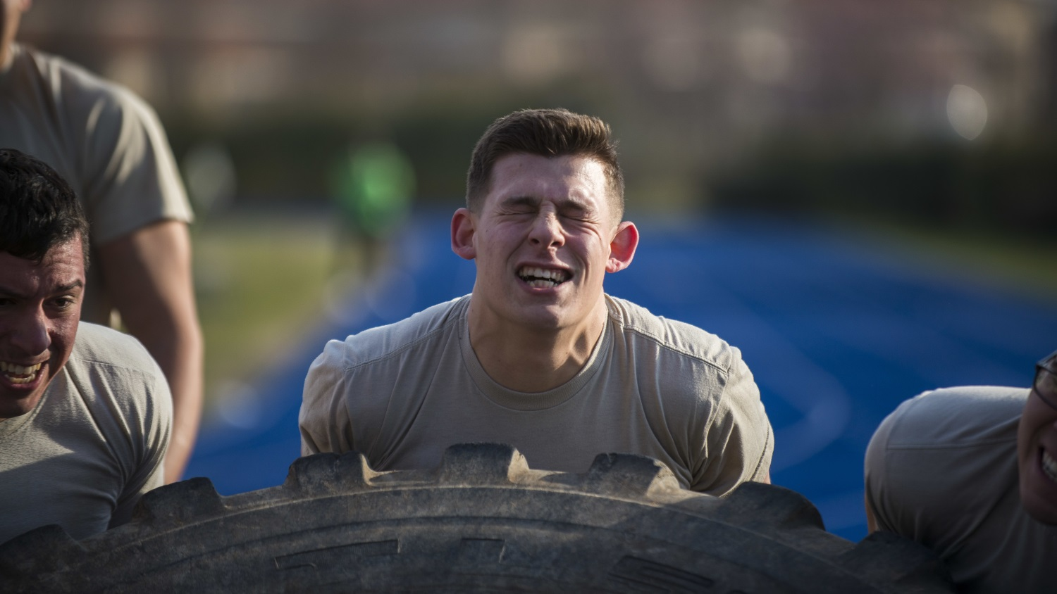 Airman 1st Class Nicholas Castellucci, 724th Air Mobility Squadron member, flips a tire with his teammates during the first Combat Warrior Challenge at Aviano Air Base, March 14, 2017. The four-day competition included obstacles such as a wall climb, tire flip, and kettle bell carry. (USenior Airman Cory W. Bush/Air Force)