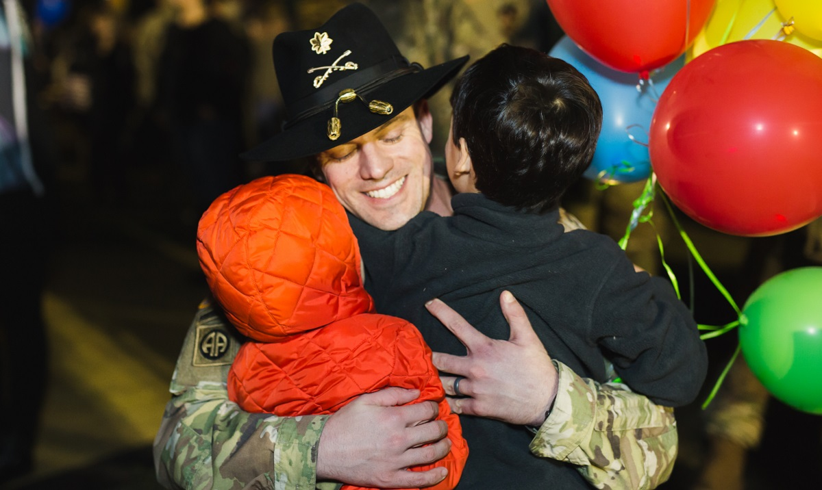 Army Maj. Matt Miller is welcomed home by his sons at Fort Hood, Texas, after a deployment. (Courtesy of Blue Star Families)