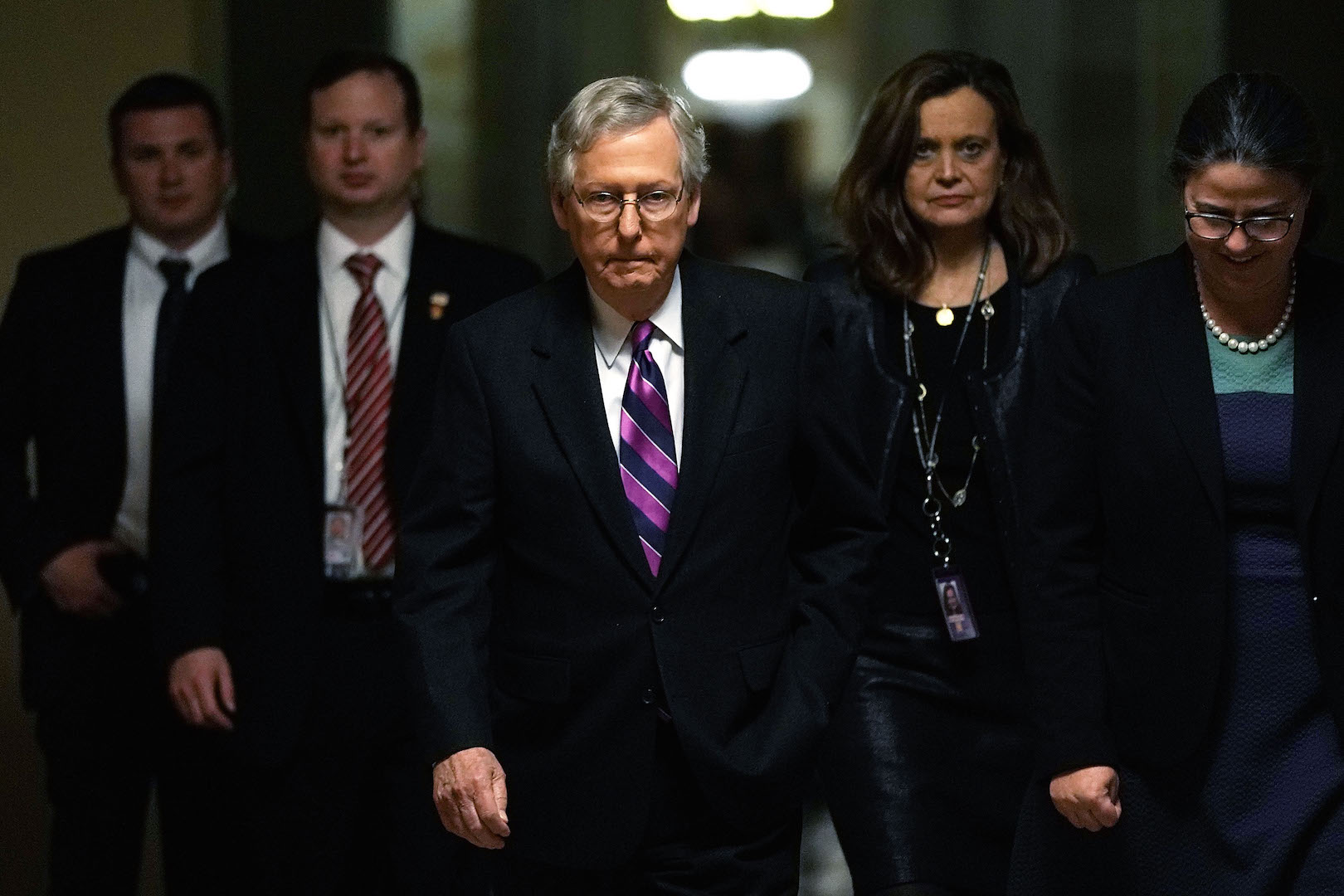 In this file photo, U.S. Senate Majority Leader Sen. Mitch McConnell, R-Ky., (center) walks toward the Senate chamber with his aides. In the partisan blame game ahead of a possible shutdown, Republicans and Democrats accused each other of hurting the military. (Alex Wong/Getty Images)